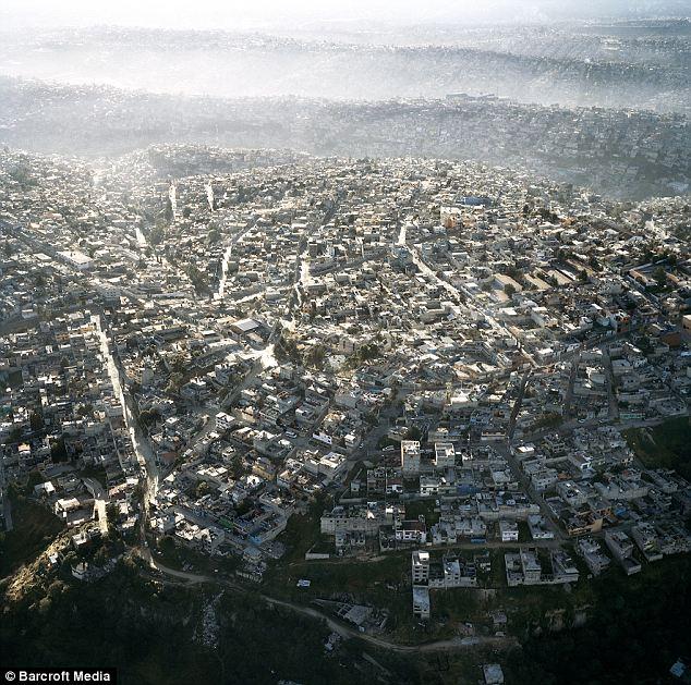 Interminables: Casas lejos sin fin de la ciudad de México y el ondular de las olas de la humanidad a kilómetros de distancia, la creación de la ciudad más poblada en el hemisferio occidental