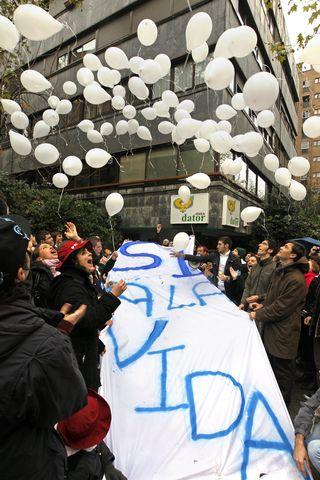Jóvenes sueltan globos en un acto ante la clínica Dator de Madrid. / ULY MARTÍN