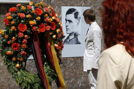 Un joven observa el retrato del coronel von Stauffenberg, líder de la operación. | Reuters