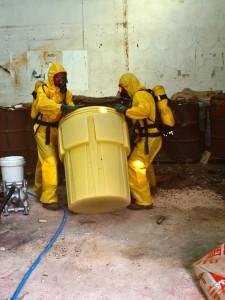 Dos operarios manejan un bidón con residuos líquidos peligrosos de Inquinosa